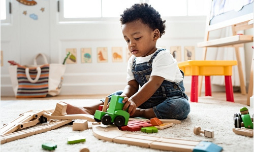 A child plays with toys on the floor.